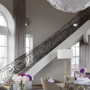 This is a look at the inside of the large dome of the penthouse that has a curved staircase with intricate wrought iron railings. This large circular room is also adorned with large arched windows that bring in natural lighting and provide a sweeping view of the city. Image courtesy of Toptenrealestatedeals.com.