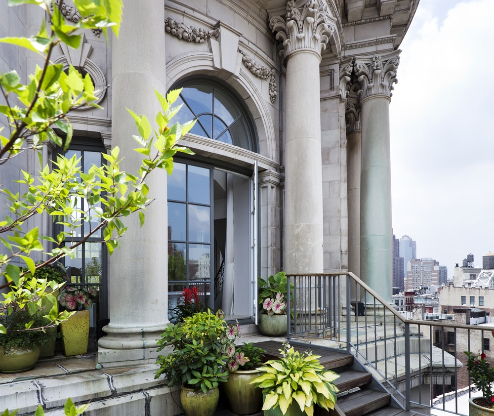 This is a look at the glass doors of the penthouse that leads to this outdoor area festooned with various potted plants that bring color to the gray exteriors adorned with tall pillars. Image courtesy of Toptenrealestatedeals.com.
