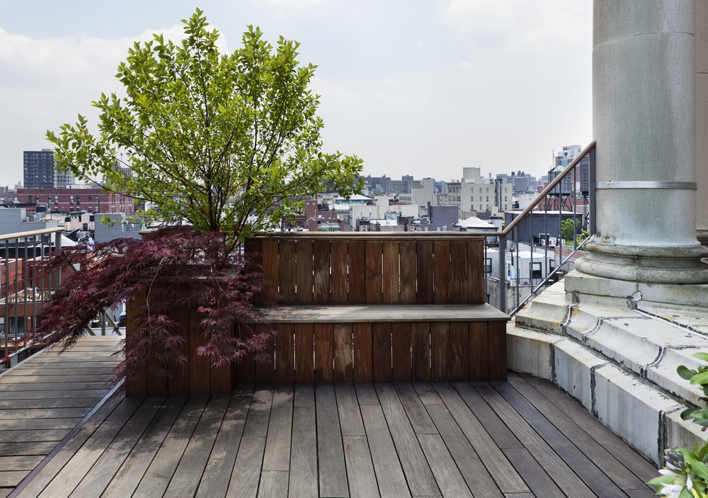 This is another wooden built-in bench at the side of the terrace. It has a built-in planter as well with a small tree that provides shade to the bench. You can also see here the wooden deck flooring of the area. Image courtesy of Toptenrealestatedeals.com.