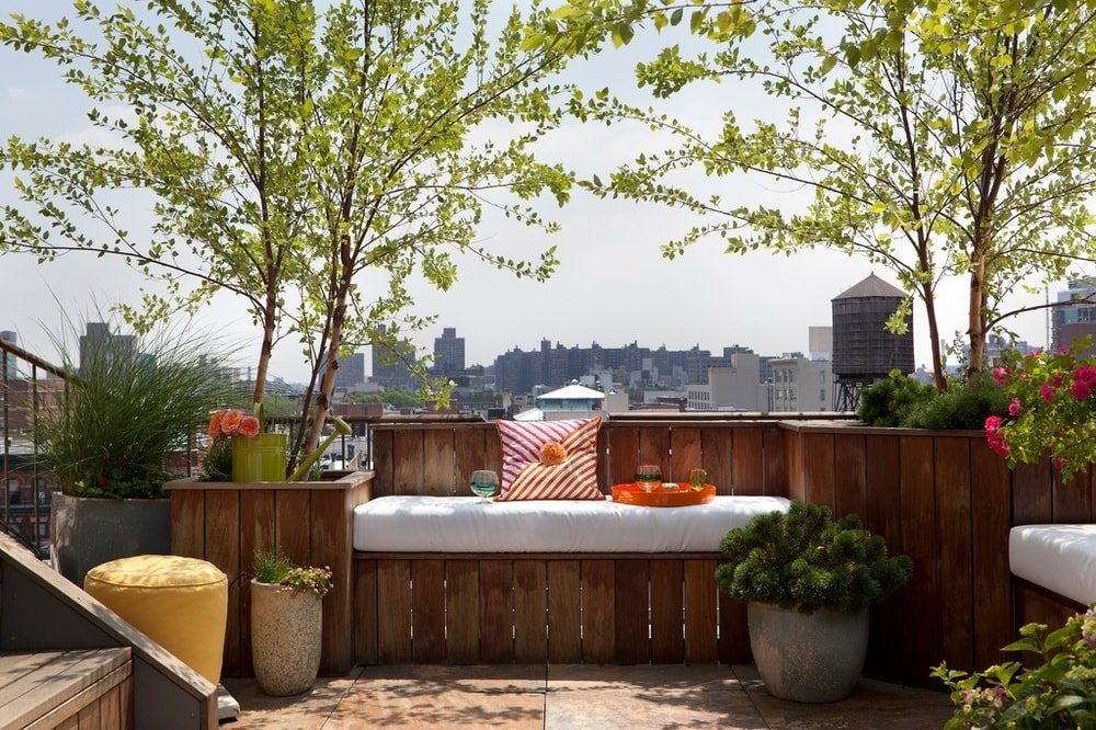 This is a close look at the side of the large terrace of the penthouse. This is fitted with a rustic wooden built-in bench with cushion to serve as a comfortable place to gaze at the city skyline as well as a reading nook adorned with various potted plants. Image courtesy of Toptenrealestatedeals.com.