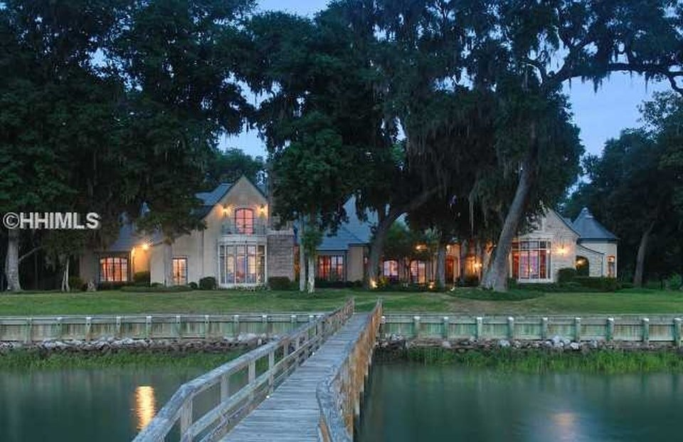 This is a view of the back of the house from the vantage of the wooden walkway to the deep water dock of the property. You can see here the warm lights of the house that makes it stand out against the tall trees. Image courtesy of Toptenrealestatedeals.com.