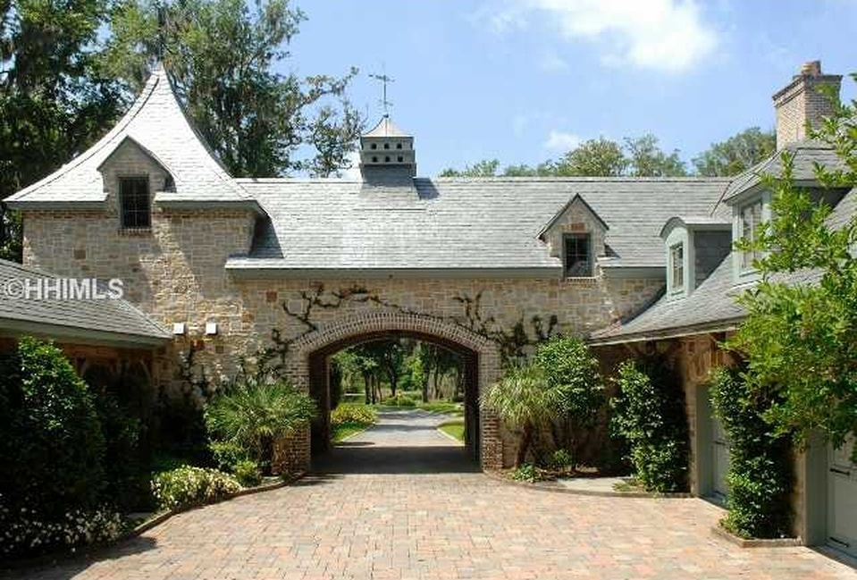 This side of the house showcases a large archway from the driveway. It is flanked with shrubs and medium-sized trees to bring color to the textured stone exteriors of the house. Image courtesy of Toptenrealestatedeals.com.