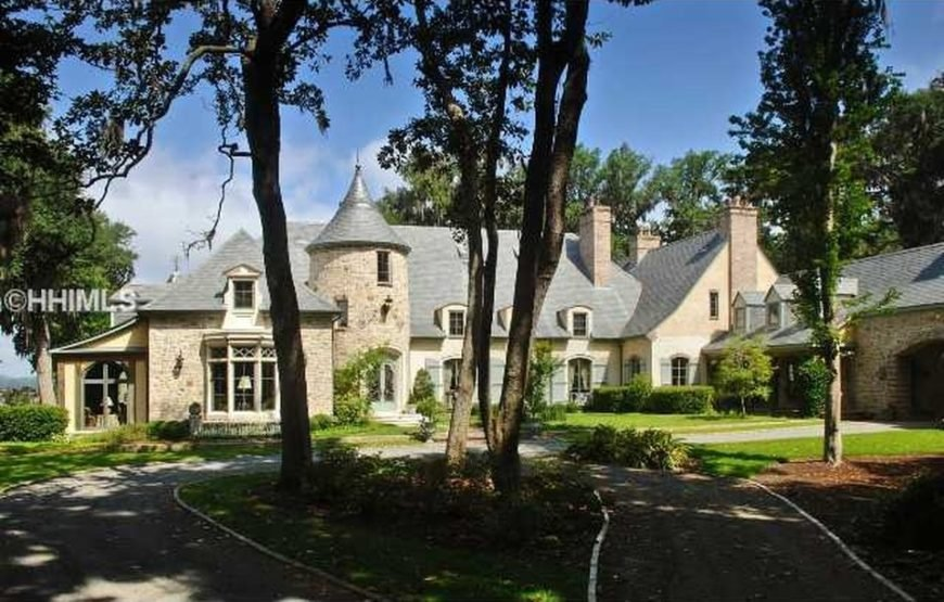 This is the front view of the mansion. It has gray roofs that match well with the textured exterior walls. These are then complemented by the large windows, tall chimneys and tall trees of the landscape. Image courtesy of Toptenrealestatedeals.com.