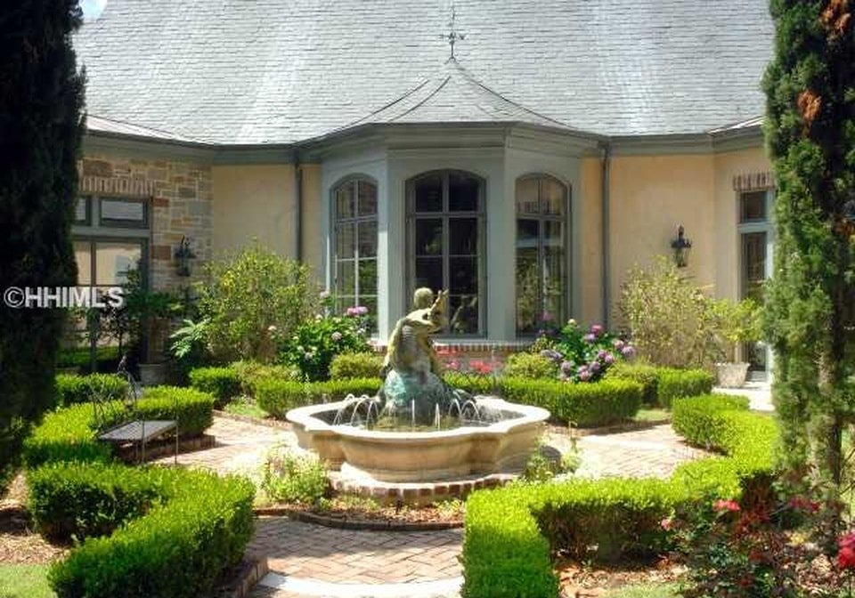 This garden has well-maintained shrubs surrounding the large stone fountain in the middle that matches the walkways and the exterior walls of the house. Image courtesy of Toptenrealestatedeals.com.