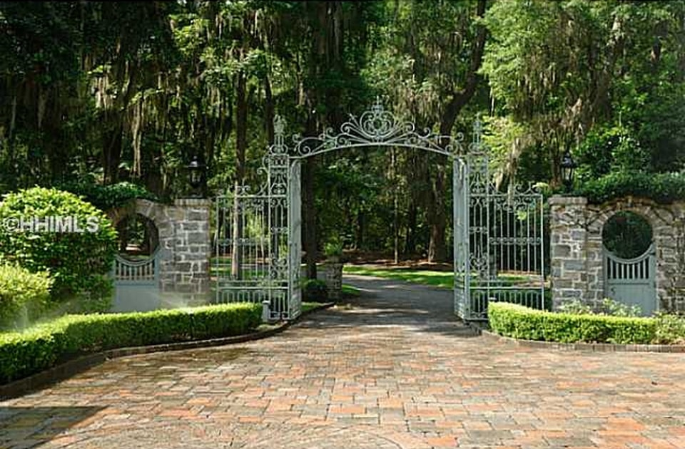 This is the outer gate of the property. It has a distinctive southern plantation-style look to it adorned with tall trees and well-maintained shrubs. Image courtesy of Toptenrealestatedeals.com.