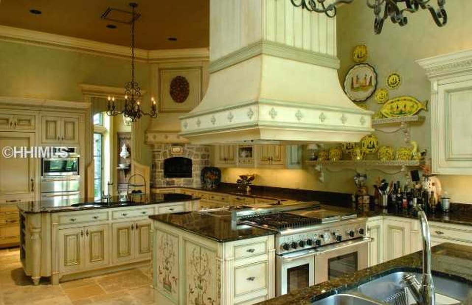 The kitchen has a consistent beige tone to the cabinetry and peninsula. This matches with the tone of the large vent hood over the cooking area. Image courtesy of Toptenrealestatedeals.com.