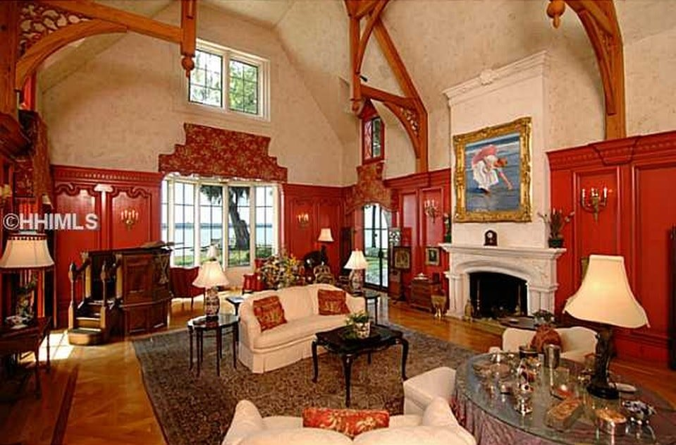 This is a spacious family room with beige sofas that match the mantle of the fireplace that is topped with a colorful painting. Image courtesy of Toptenrealestatedeals.com.
