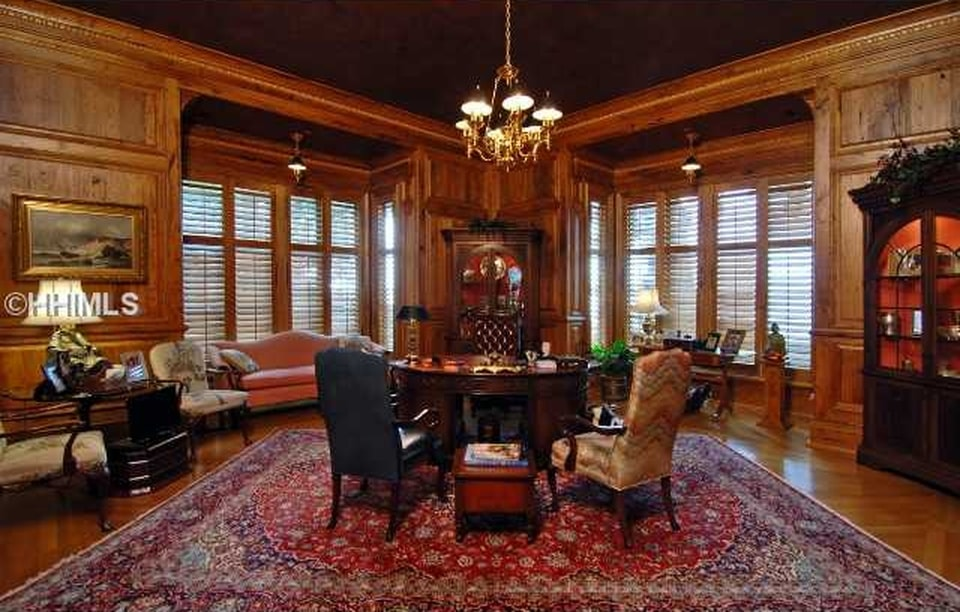 This home office has dark wooden walls with two large sets of shuttered windows. This is topped with a dark brown ceiling that matches the tone of the wooden desk in the middle of the large red patterned area rug. Image courtesy of Toptenrealestatedeals.com.