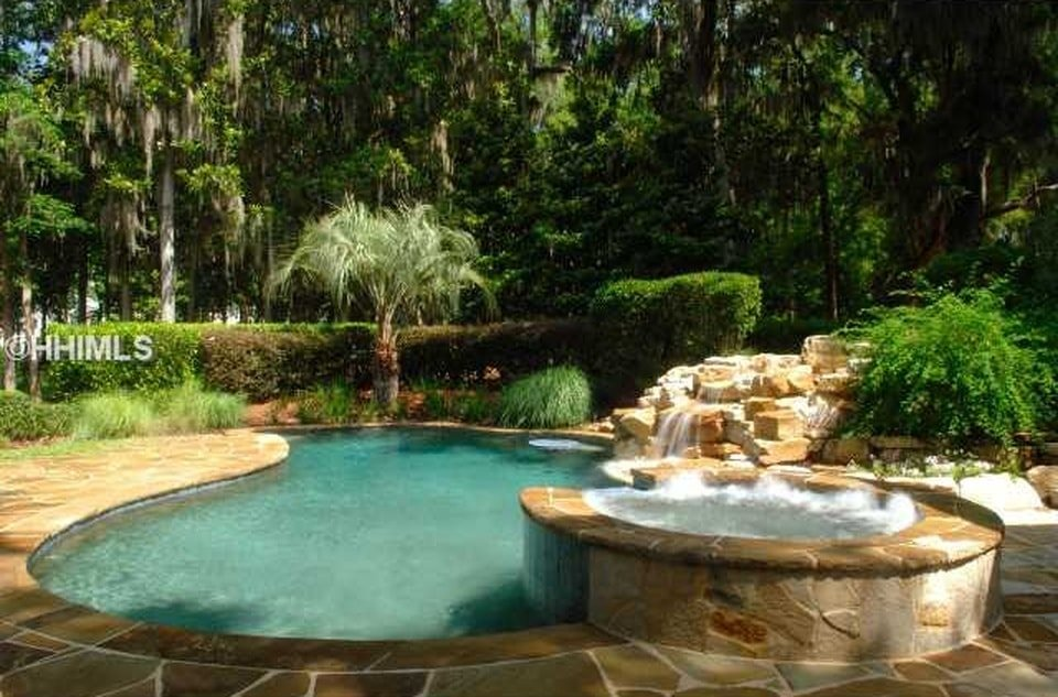 This is a close look at the backyard pool surrounded by mosaic stone walkways extending to the elevated jacuzzi-type pool beside the swimming pool. Image courtesy of Toptenrealestatedeals.com.