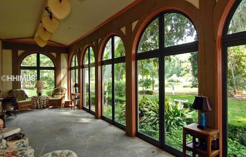 This is a sun room with arched glass windows bringing in natural lighting for the various sofas and armchairs on the gray concrete floor. Image courtesy of Toptenrealestatedeals.com.