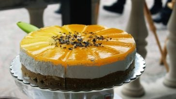 A full sliced cake of orange creamsicle cheesecake.
