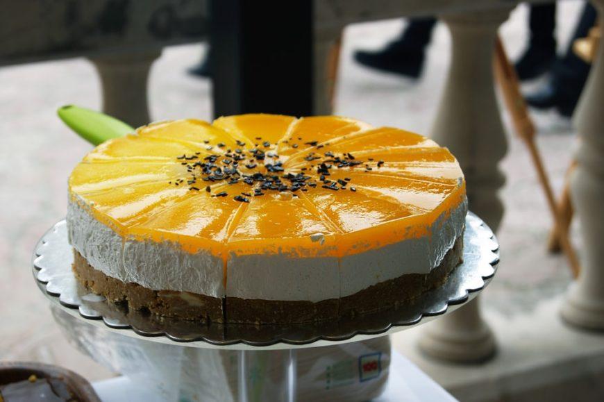 A full sliced cake of orange creamsicle cheesecake.