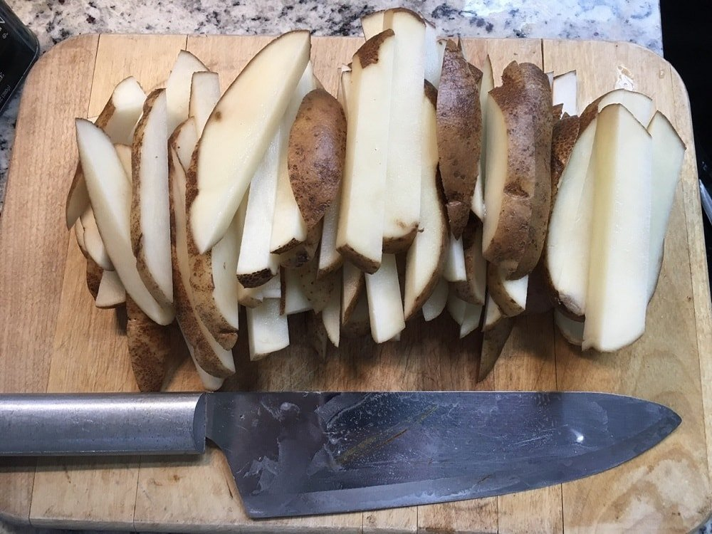 A bunch of potato slices with skin on a chopping board.