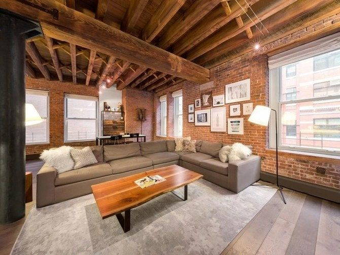 One of her Tribeca apartments offer this living space with a large L-shaped sofa set surrounded by red brick walls. Images courtesy of Toptenrealestatedeals.com.