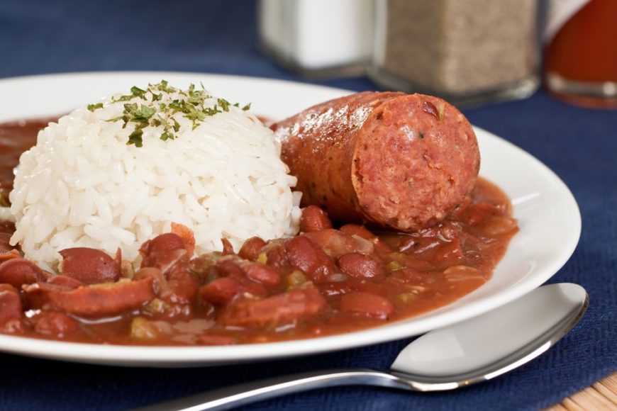 A mouth-watering plate of red beans and rice with a piece of sausage.