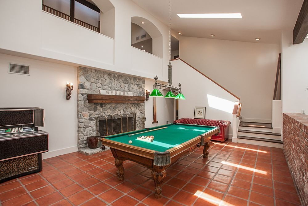 A game room featuring a billiards table set near the fireplace. Image courtesy of Toptenrealestatedeals.com.