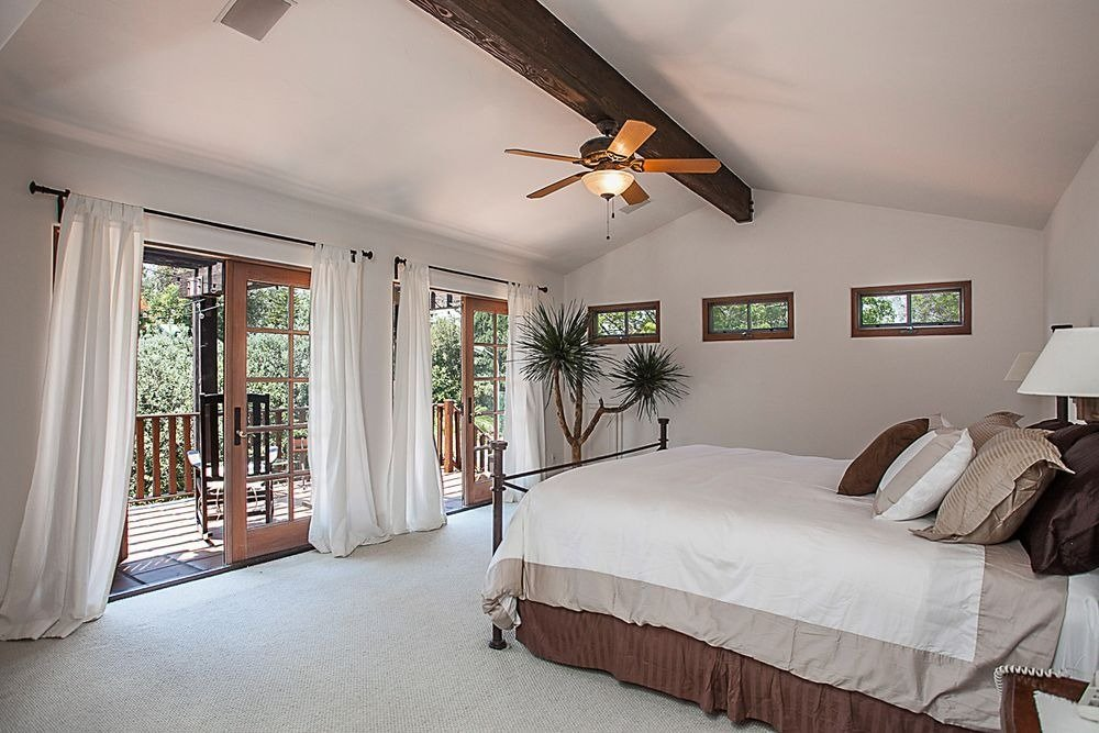 A bedroom suite with doorways leading to a private balcony. Image courtesy of Toptenrealestatedeals.com.