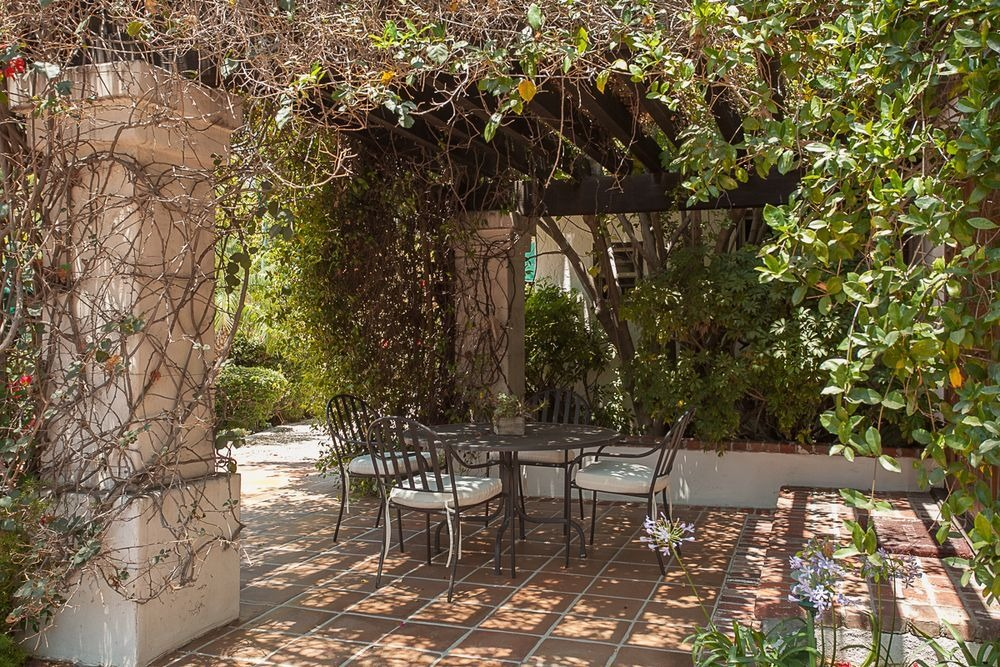 An outdoor dining table set surrounded by the outdoor plants of the property. Image courtesy of Toptenrealestatedeals.com.