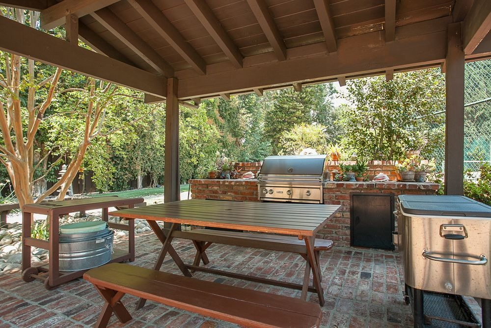 Outdoor dining and kitchen with a brick counter and a wooden table set. Image courtesy of Toptenrealestatedeals.com.