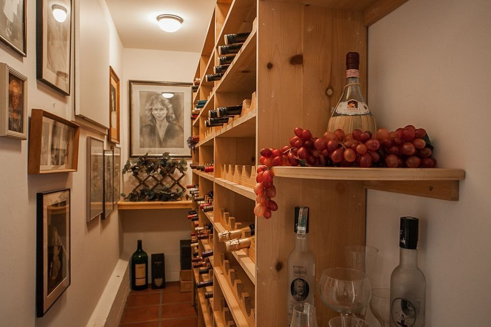 A narrow wine cellar featuring multiple wooden bottle racks. Image courtesy of Toptenrealestatedeals.com.
