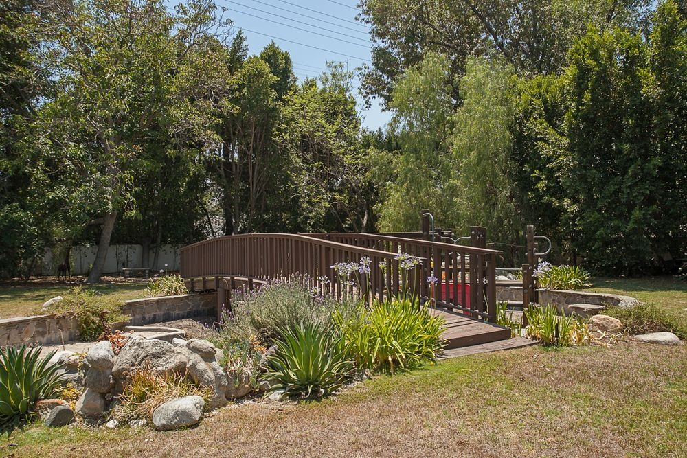 Here's a wooden bridge on the home's lush garden area. Image courtesy of Toptenrealestatedeals.com.
