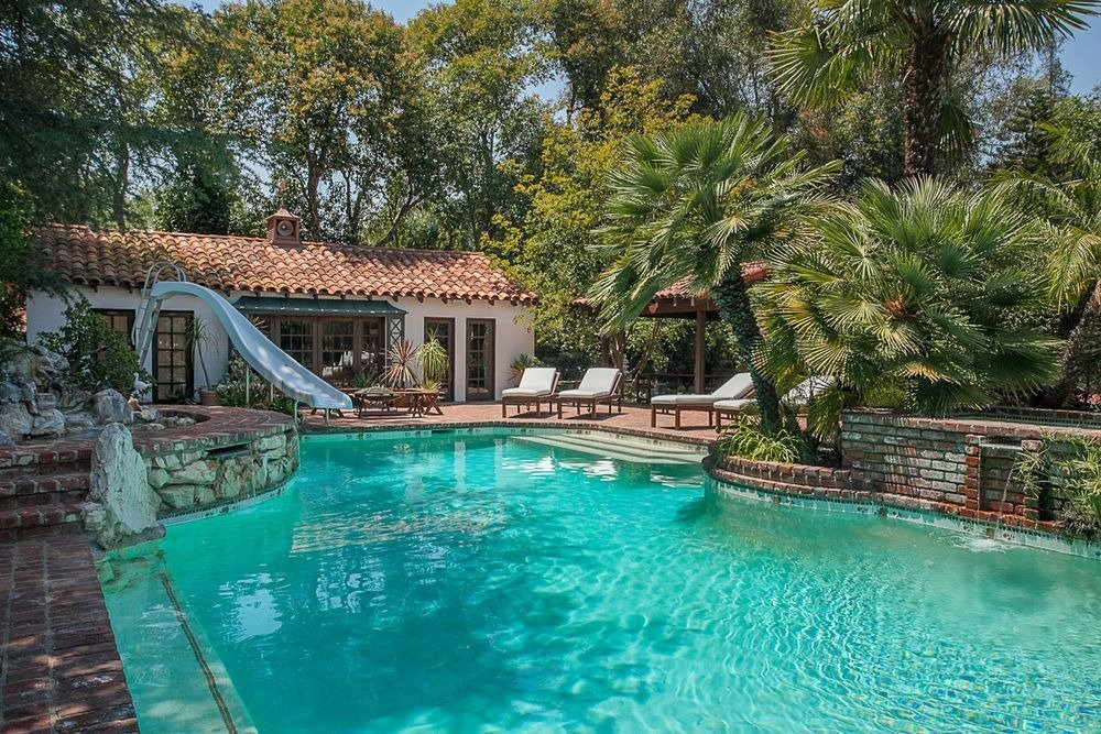 Closer look at the home's custom swimming pool with a slide and lush garden plants and trees surrounding it. Image courtesy of Toptenrealestatedeals.com.