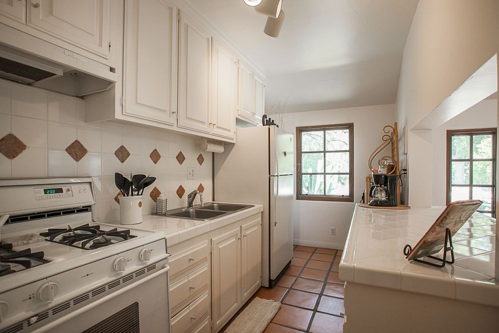 A smaller kitchen area with a white kitchen countertop. Image courtesy of Toptenrealestatedeals.com.