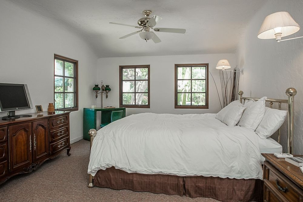 Bedroom featuring a large cozy bed set lighted by two wall lights. Image courtesy of Toptenrealestatedeals.com.
