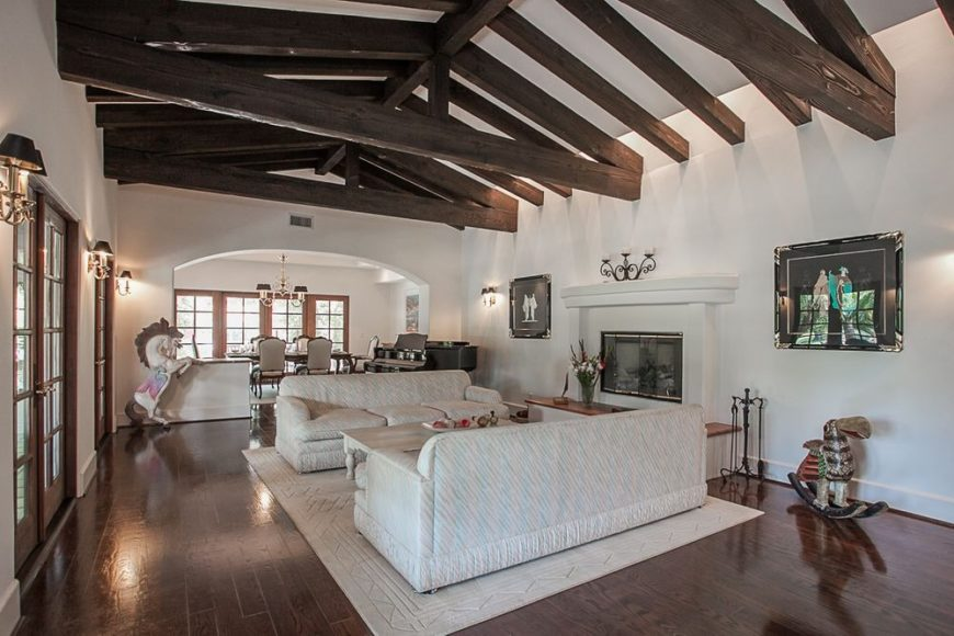 Spacious living space featuring a rustic ceiling, hardwood flooring and white walls. This living space comes with a pair of cozy couches and a fireplace. Image courtesy of Toptenrealestatedeals.com.