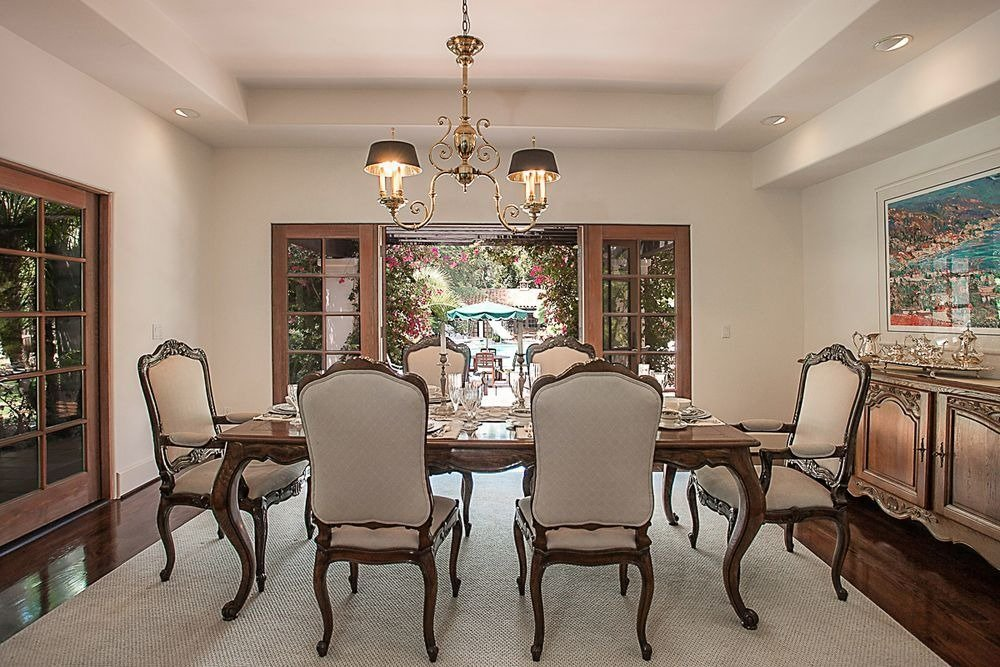Formal dining featuring a classy dining table set on top of an area rug lighted by a stunning ceiling light. Image courtesy of Toptenrealestatedeals.com.