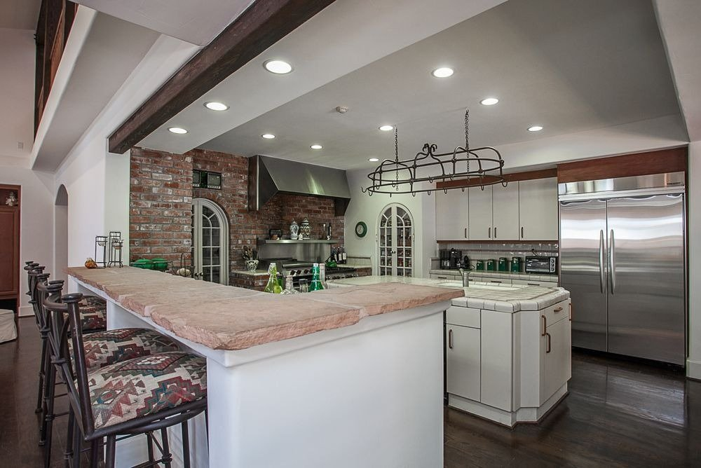 Large kitchen with a separate bar counter and a center island. Image courtesy of Toptenrealestatedeals.com.