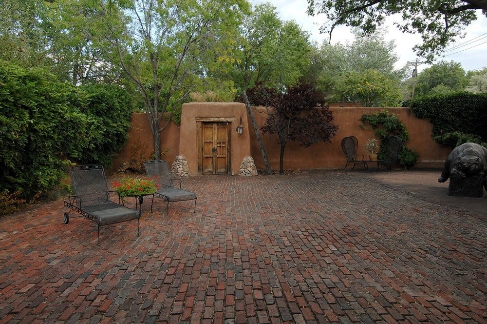 The courtyard of the compound has red brick flooring that pairs well with the surrounding earthy stone walls and the trees of the landscape that serve as background and shade for the sitting area. Image courtesy of Toptenrealestatedeals.com.