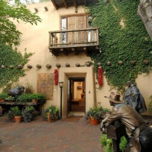 This is a view of the front of the house with beige walls adorned with creeping plants, statues and various plants that flank the entryway beneath the small wooden balcony. Image courtesy of Toptenrealestatedeals.com.