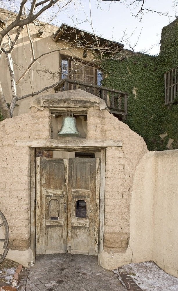 This is the main gate of the compound with a rustic wooden gate housed by a large stone structure with a bell. Image courtesy of Toptenrealestatedeals.com.