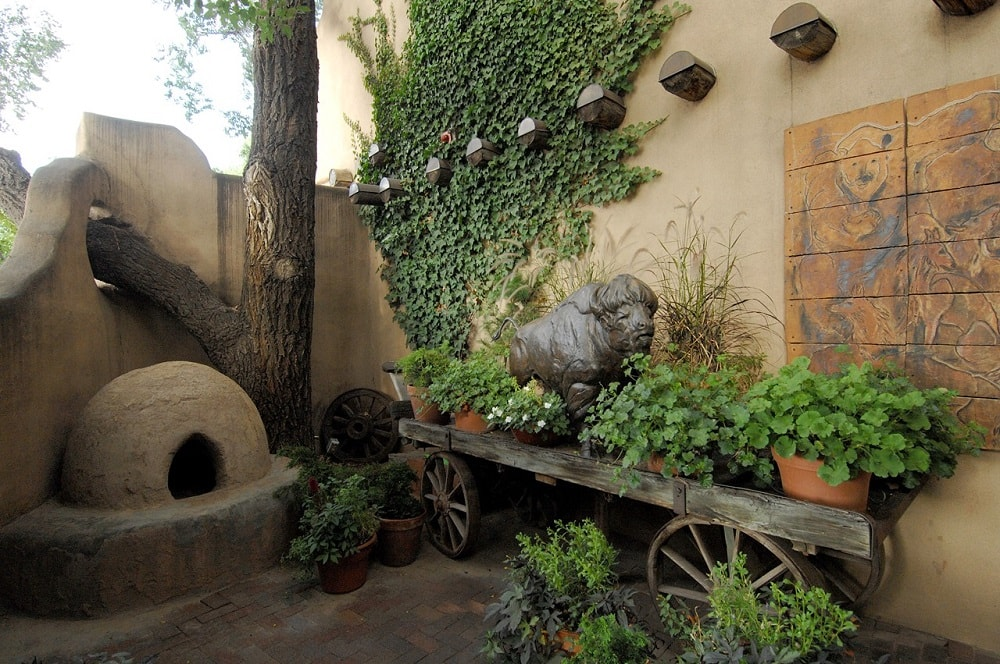 This is a closer look at the decorative landscaping at the side of the entryway of the house. It has a sculpture on an old rustic cart along with potted plants. Image courtesy of Toptenrealestatedeals.com.