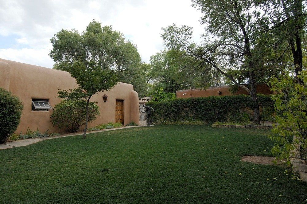 This is a look at the grass lawn inside with tall shrubs and trees that bring contrast to the earthy tones of the exterior walls. Image courtesy of Toptenrealestatedeals.com.