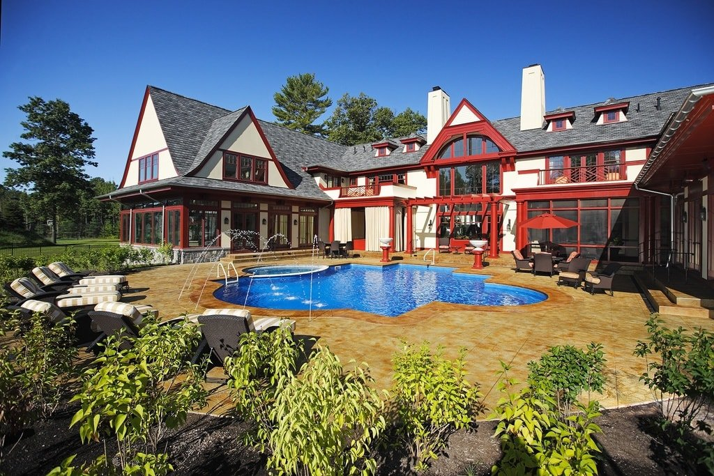 This is a view of the back of the house that has a pool surrounded by beige tiles. This view also showcases the vibrant red accents of the house exteriors along with large glass windows. Image courtesy of Toptenrealestatedeals.com.