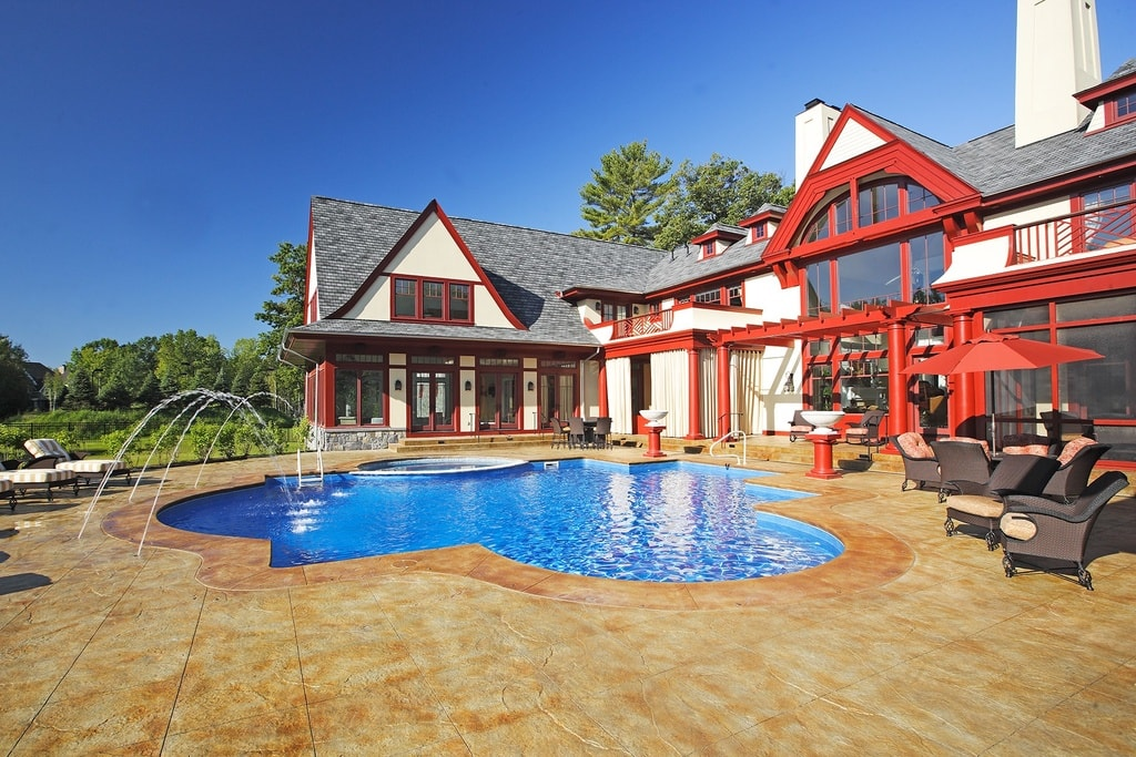 This other look of the back of the house gives us a look at the beige tiles surrounding the pool. This tone makes the red accents of the house stand out. Image courtesy of Toptenrealestatedeals.com.