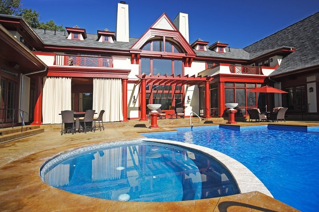 This view of the back of the house showcases the vibrant red accents of the house exteriors along with the large glass windows. Image courtesy of Toptenrealestatedeals.com.