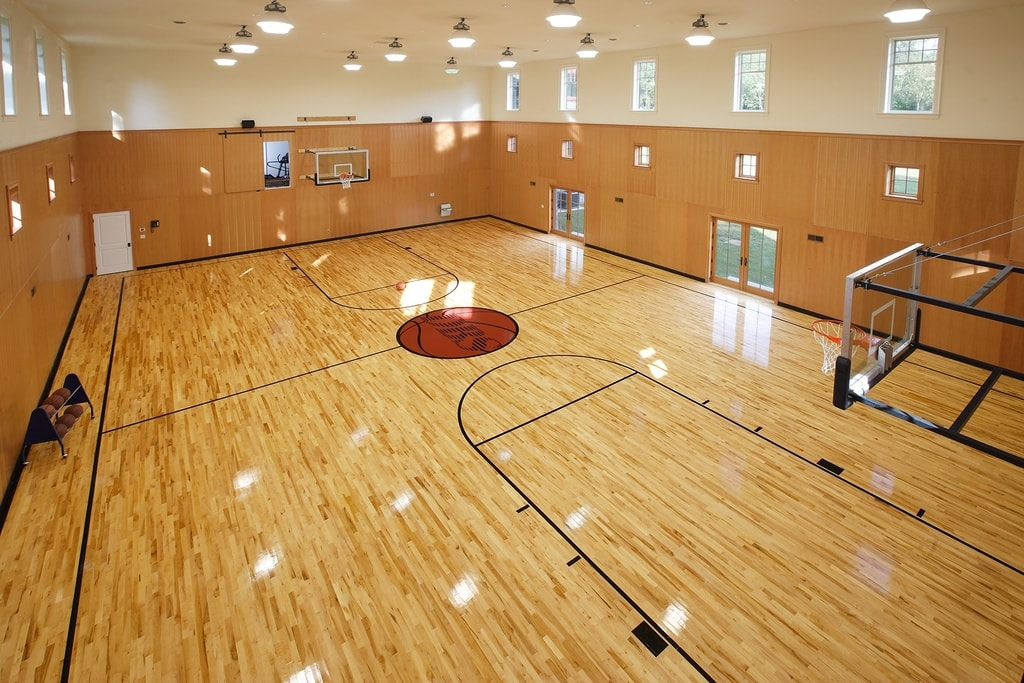 This is the professional-size indoor basketball court of the mansion. It is well-lit by the multiple lights of the tall ceiling. Image courtesy of Toptenrealestatedeals.com.
