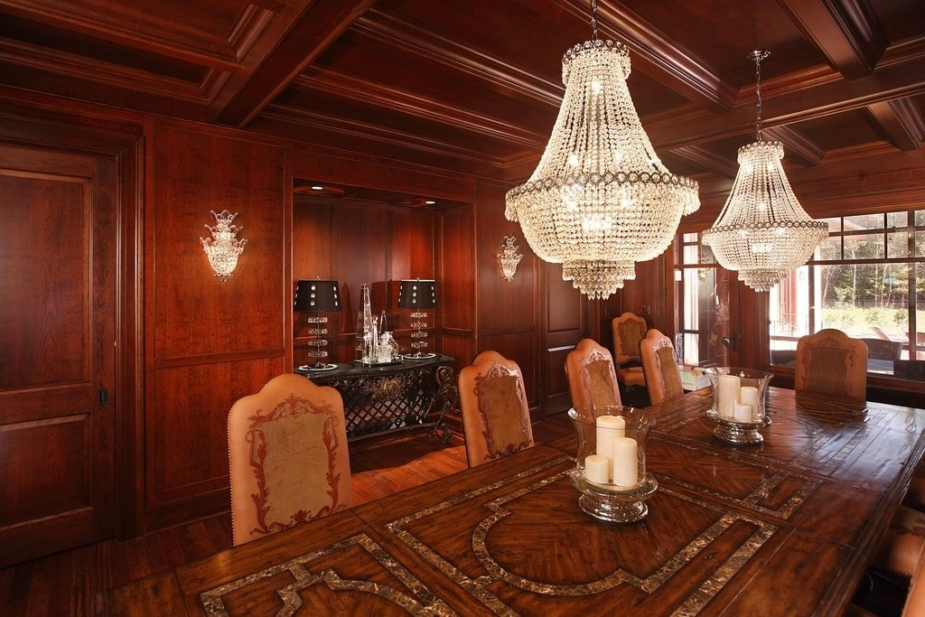 The formal dining room has a large rectangular dining table topped with a couple of decorative chandeliers hanging from a dark wooden coffered ceiling. Image courtesy of Toptenrealestatedeals.com.