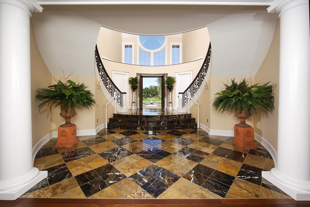 Upon entry, you are welcomed by this grand foyer that has checkered patterns to its black and brown marble floor. Image courtesy of Toptenrealestatedeals.com.