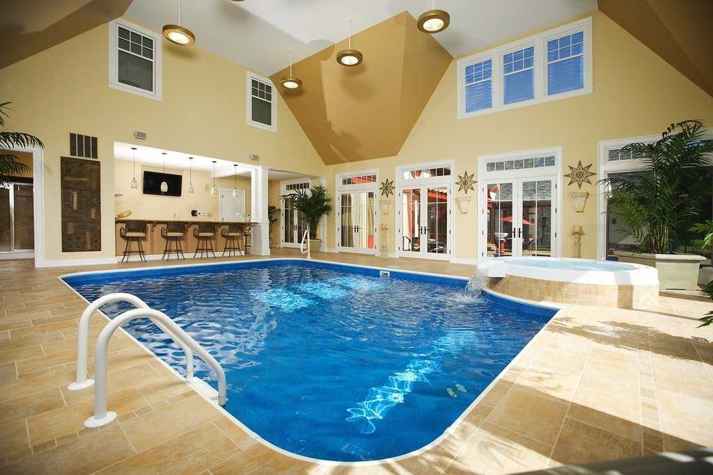 This is the indoor pool with a tall ceiling, beige walls that has transom windows and a pool that is surrounded by beige tiles. Image courtesy of Toptenrealestatedeals.com.