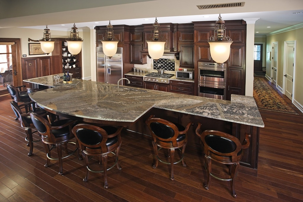 This is the kitchen that has a large kitchen island with a marble countertop and dark brown cabinetry that matches perfectly with the hardwood flooring and the wooden chairs of the breakfast bar. Image courtesy of Toptenrealestatedeals.com.