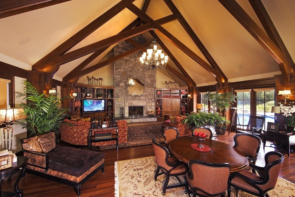 This is a look at the great room with a living room on the far side that has a stone fireplace. Next to the living room is an informal dining area topped with a tall cathedral ceiling with exposed wooden beams. Image courtesy of Toptenrealestatedeals.com.