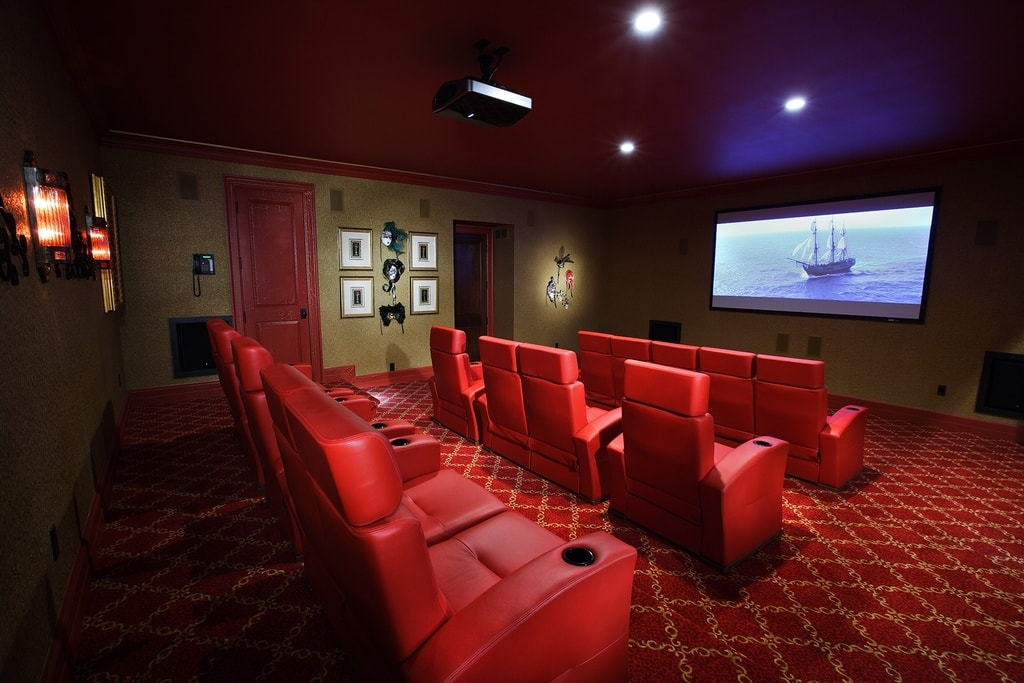 This is a multi-row home cinema theater with red leather seats to match the red patterned carpeting. Image courtesy of Toptenrealestatedeals.com.