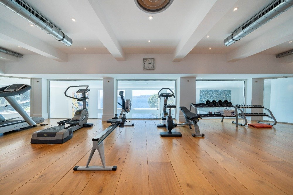 Large and fully equipped home gym featuring a white ceiling and hardwood flooring. Image courtesy of Toptenrealestatedeals.com.