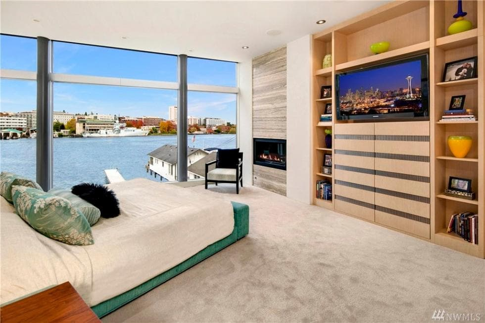 The bedroom has neutral tones to its carpeting, platform bed and built-in cabinets. These are all complemented by the views afforded by the glass walls. Image courtesy of Toptenrealestatedeals.com.