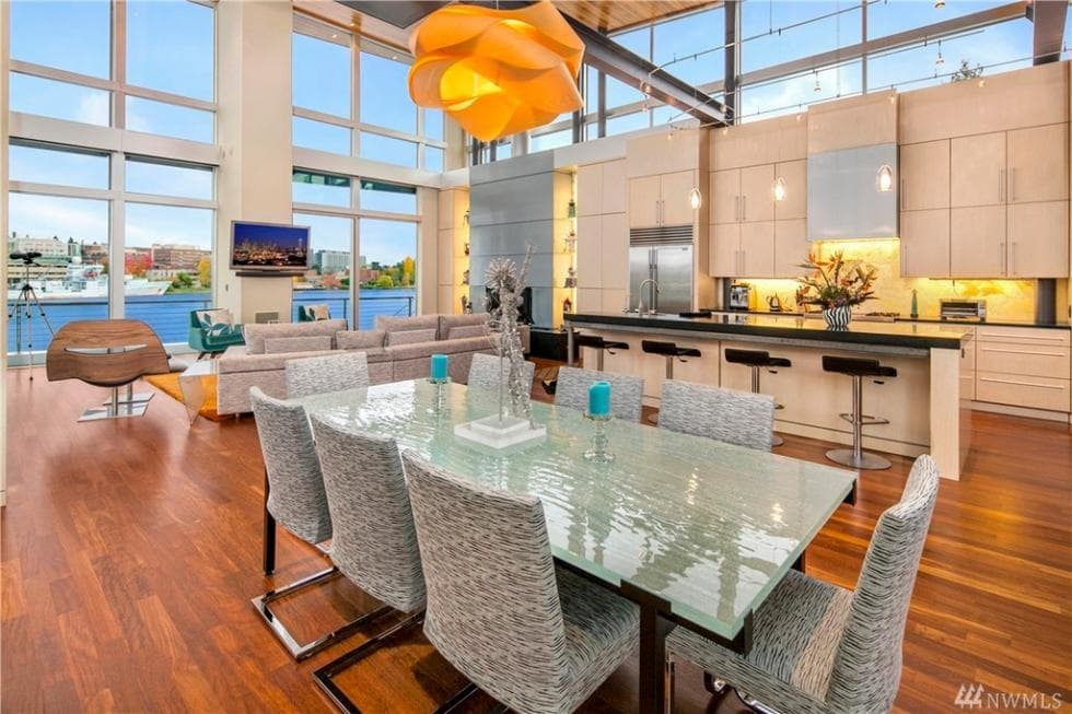 The dining area is part of the large room that also houses the kitchen and living room on the far side by the glass walls. The dining area has a glass-top dining table topped with a decorative pendant light hanging from the tall ceiling. Image courtesy of Toptenrealestatedeals.com.