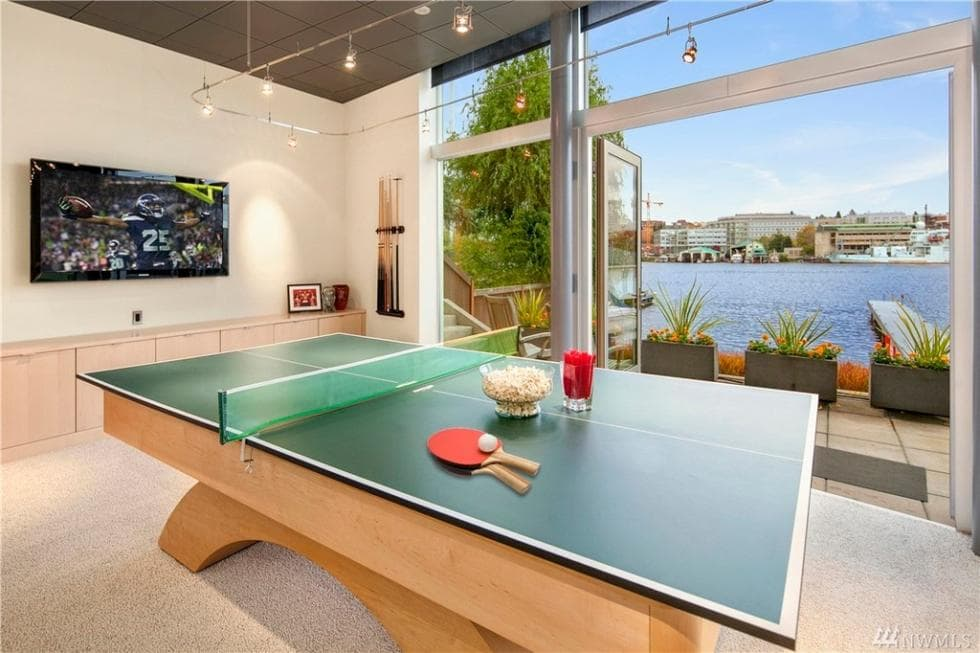 The game room has a large ping pong table illuminated by the modern lighting of the tall ceiling along with the natural lights coming in from the glass walls and doors that have great views of the lake. Image courtesy of Toptenrealestatedeals.com.